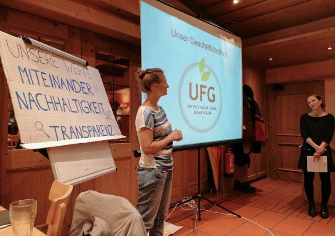 Teaserbild Veranstaltungen – Laura und Wiebke bei einer Veranstaltung vor einer Präsentation auf einer Leinwand