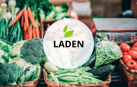 """Foto loser Gemüseartikel, die in Körben liegen. Davor der Schriftzug """"Laden"""" und die grünen Blätter aus dem Logo"""