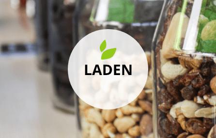 Ausschnitt mehrerer nebeneinander stehender Glasgefäße, die mit Nüssen und Studentenfutter gefüllt sind. Darüber mittig ein transparenter weißer Kreis mit dem Begriff LADEN. Darüber befinden sich zwei kleine grafische grüne Blätter.