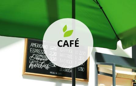 Eine schwarze Tafel mit goldenem Rahmen auf dem sehr kunstvoll die Kaffeekarte von Hand darauf geschrieben ist. Davor steht ein großer grüner Schirm. Eine Ecke des Gebäckregals ist noch zu erkennen. Mittig darauf platziert befindet sich ein transparenter weißer Kreis mit schwarzer Schrift. Der Begriff lautet CAFÉ. Darüber befinden sich zwei kleine grüne grafische Blätter.