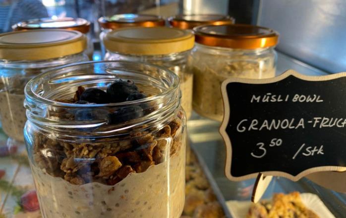"""Appetitlich angerichtete Granola mit Frucht in einem Glas mit offenem Deckel. Daneben ein handbemaltes Schild mit dem Preis 3,50 € pro Stück und die Bezeichnung """"Granola-Frucht-Müsli-Bowl"""""""
